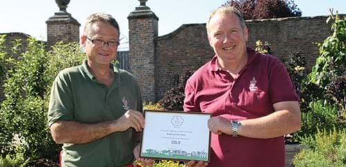 Tom and Adrian displaying their Gold award certificate in the Kitchen Garden