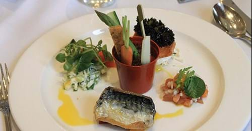 The fish is plated with vegetables in a plant pot and side dressings