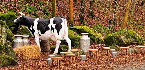 Cow model stands next to milk churns and eight milking stools and pails
