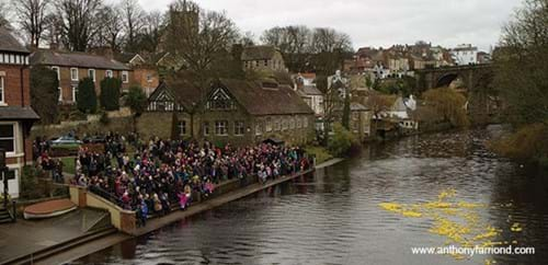 People crowd by the banks of the river watching the Duck Race - photo courtesy of anthonyfarrimond.com