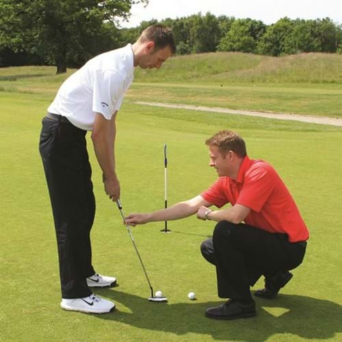 A man is lining up a shot, as his tutor is crouched beside him helping him to correct his club position.
