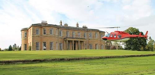 Helicopter flying across the front of Rudding House