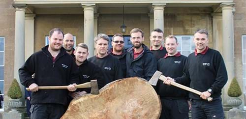 Rudding Park Greenkeepers poised with axes beside a felled tree