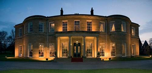Rudding House, early evening. The house is lit and the sky is dusky behind it.