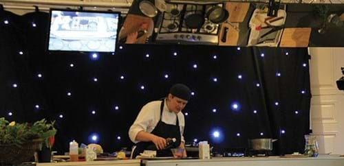 Steph adds oil to the dish she is preparing on stage