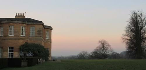 Sun set looking out over parkland with Rudding House in the foreground