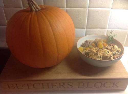 Chilli pork dish sits next to a pumpkin on a large wooden block