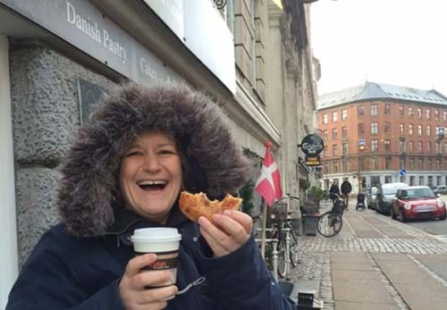 Steph, wrapped up for the cold, enjoys a pastry and coffee