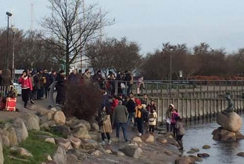 People crowd beside the lake with the Little Mermaid sculpture