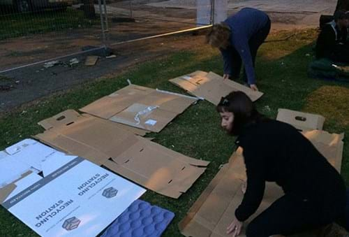 Setting up camp - laying cardboard boxes out on the grass