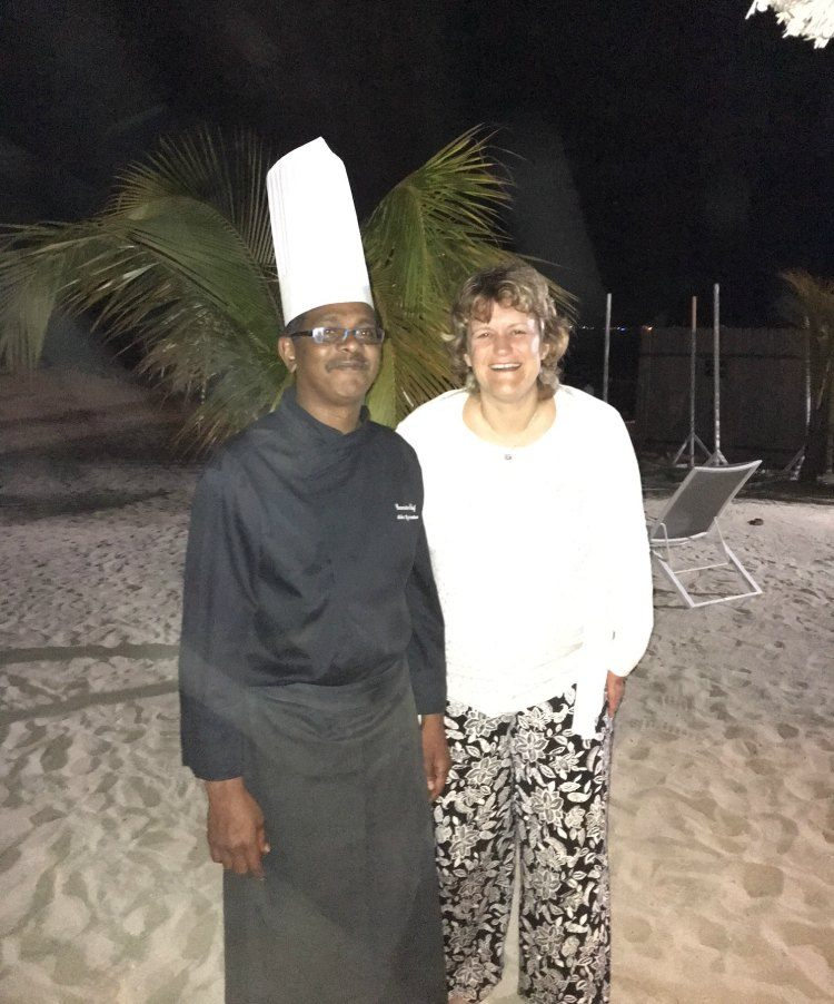 Mike the Head Chef stands next to Steph on the beach. He wears a black uniform with a tall white chef's hat.