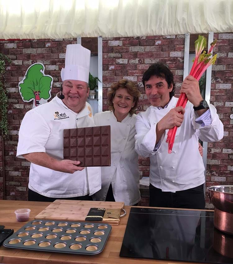 David holds a slab of chocolate up which is about a quarter the size of the hob! Jean-Christophe holds up some sticks of rhubarb and Steph stands between the two men, smiling.