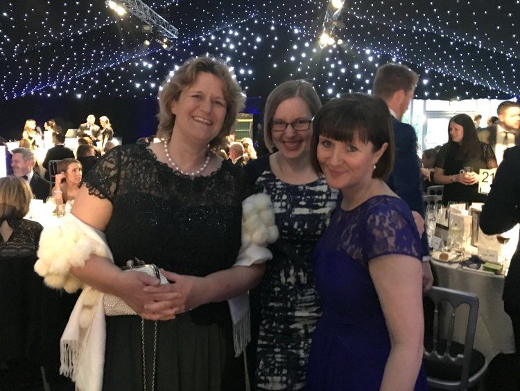 Steph stands on the left in a black dress with a white wrap draped over her arms. In the middle, Gill wears a patterned navy and white shift dress, whilst on the right Nicola is in a blue lace dress.