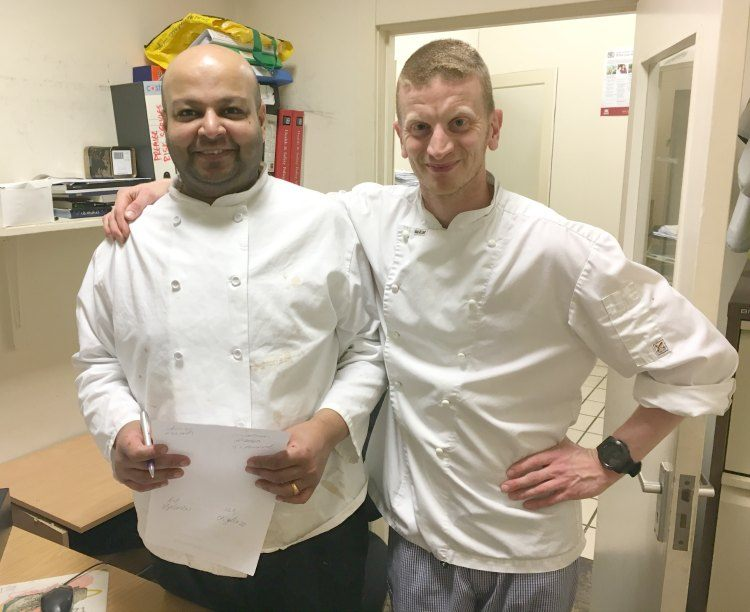 The two chefs,  in their whites, stand together just inside their office.