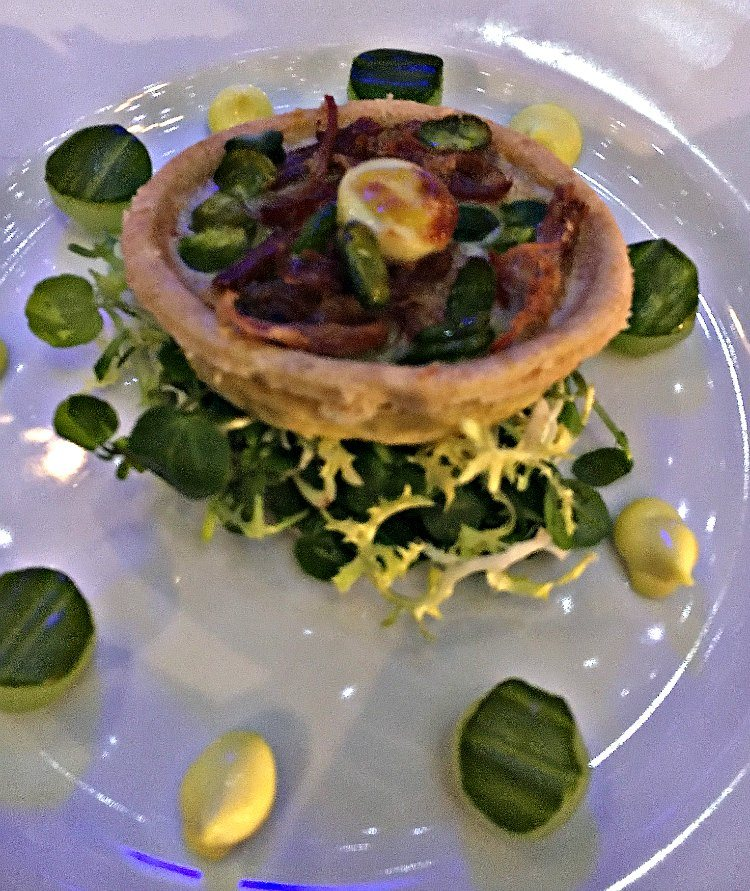 The tart sits centrally on a bed of salad, surrounded by alternate cucumber slices and mustard dots. The primary tones are green and lemon, giving a fresh feel.