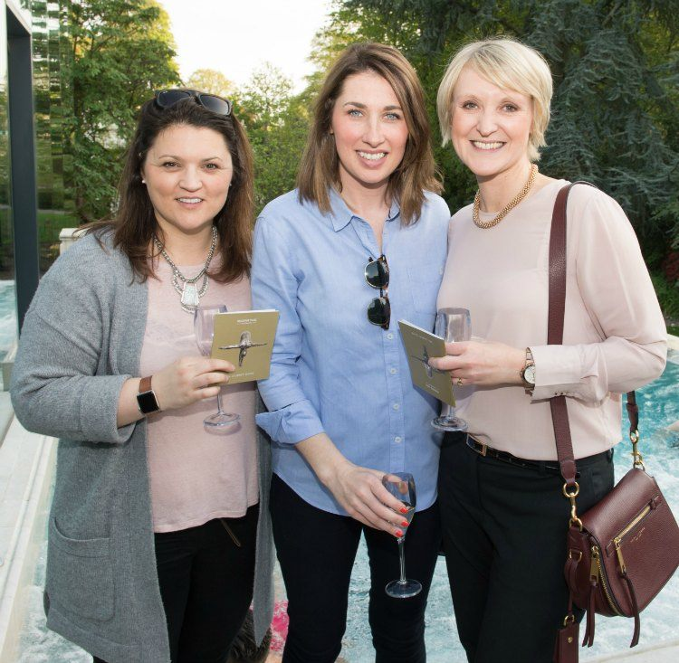 Caroline, Nicola and Kate stand just in front of the pool, holding glasses and Spa leaflets.