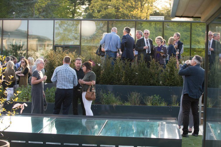 Guests stand in the Roof Top Garden, in front of the entrance to the Roof Top Spa, talking and drinking