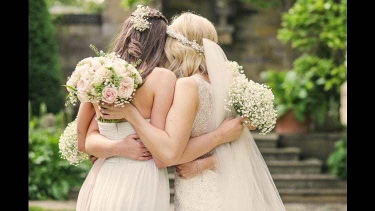 Bridesmaids hugging on the Jupiter Terrace at Rudding Park