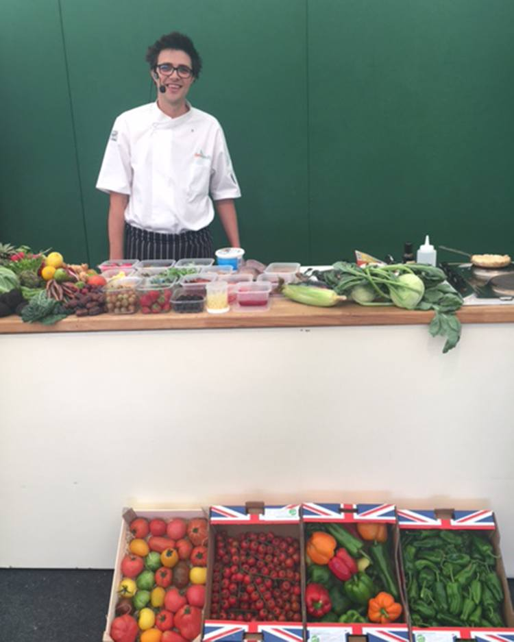 Robert Ramsden stands in front of a demo table crammed with fruit and veg, with more boxes in front of the table.