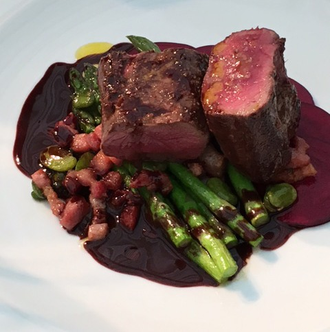 Generous chunks of venison sit on a bed of asparagus with chocolate sauce