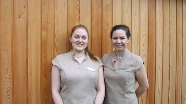 Kelli and Zoe smiling in front of the sauna