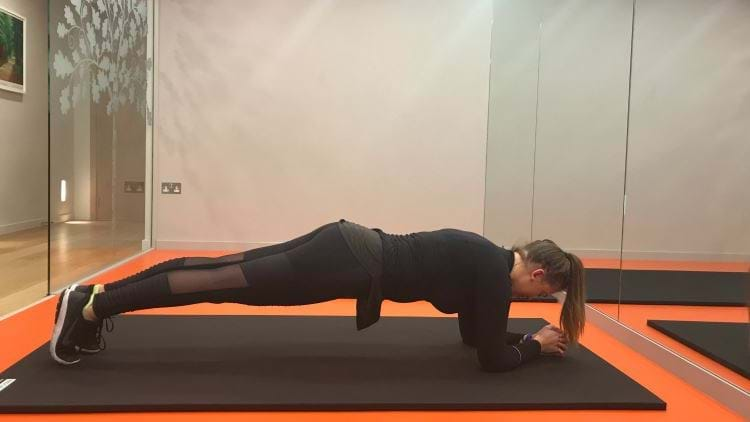 Female personal trainer showing the plank position in gym area