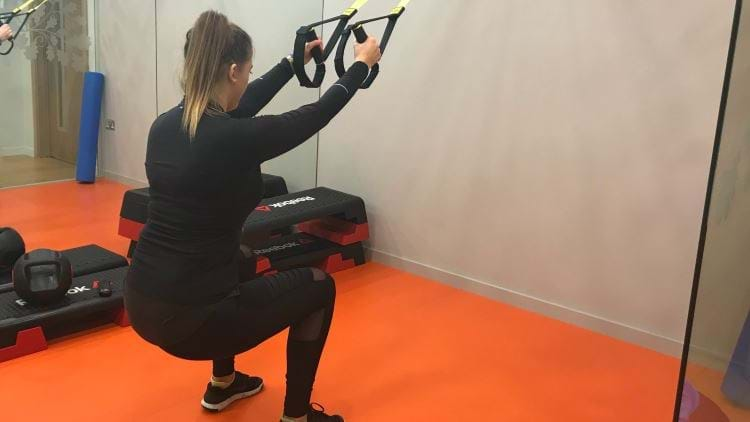 Female personal trainer in the gym showing the squat